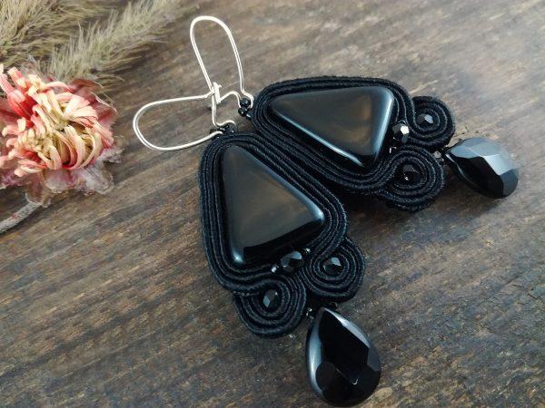 Kolczyki sutasz w kolorze czarnym ze szklanym koralikiem w kształcie trójkąta.