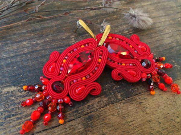Kolczyki sutasz w kolorze czerwonym, zawieszone na sztyftach ze stali chirurgicznej.